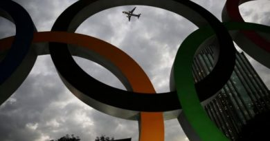 An airplane flies past Olympic rings placed at the entrance of  office building ahead of the Rio 2016 Olympic Games, in Sao Paulo, Brazil, July 19, 2016. REUTERS/Nacho Doce