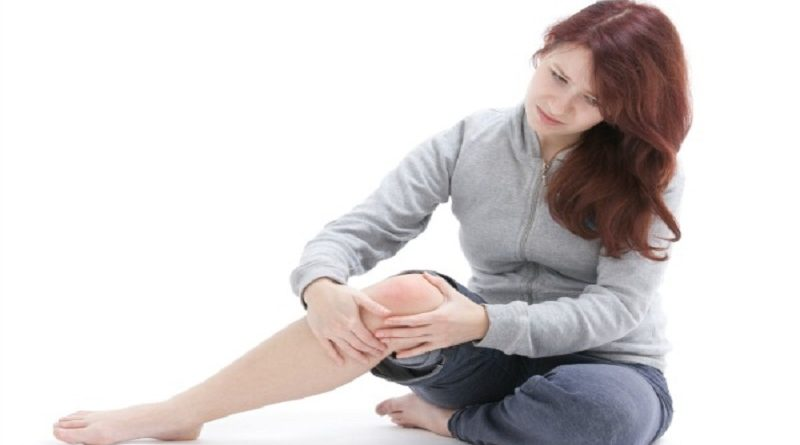 Woman palpate her painful knee. Studio shot against white background.