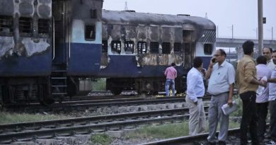People stand near vandalized train coaches in New Delhi, India, Friday, Aug. 25, 2017. Mobs rampaged across the north Indian town of Panchkula on Friday after a court declared a quasi-religious sect leader guilty of raping two of his followers. Two coaches of an empty train parked in New Delhi's Anand Vihar station were also set on fire. (AP Photo/Manish Swarup)