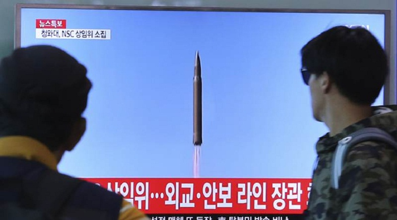 """People watch a TV screen showing a file footage of North Korea's missile launch, at the Seoul Railway Station in Seoul, South Korea, Tuesday, Aug. 29, 2017. North Korea fired a ballistic missile from its capital Pyongyang that flew over Japan before plunging into the northern Pacific Ocean, officials said Tuesday, an especially aggressive test-flight that will rattle an already anxious region.The signs read """" A National Security Council meeting will be held."""" (AP Photo/Ahn Young-joon)"""